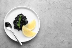 Plate with black caviar and slices of lemon. On table Stock Image