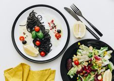 Plate of black spaghetti with tomatoes cherry and fresh summer salad. Flat lay Stock Photo