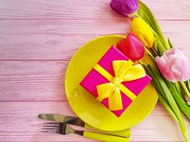 Plate, a bouquet of beautiful tulips season on a pink wooden background royalty free stock photo
