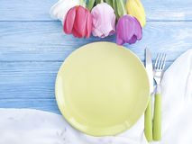 Plate, a bouquet of tulips seasonal springtime on a wooden background decorate royalty free stock photography