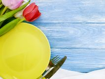 Plate, a bouquet of tulips bloom seasonal springtime on a wooden background decorate stock photo