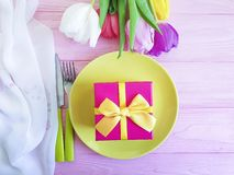 Plate, a bouquet of beautiful natural tulips celebration on a pink wooden background royalty free stock photos