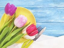 Plate, a bouquet of tulips bloom seasonal springtime on a wooden background stock photos
