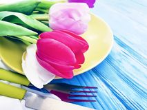 Plate, a bouquet of tulips bloom springtime on a wooden background royalty free stock photos