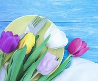 Plate, a bouquet of tulips springtime on a wooden background royalty free stock images