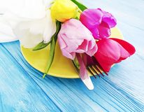 Plate, a bouquet of tulips on a wooden background royalty free stock images
