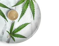 Plate with bowl of hemp lotion and leaves. On light background, top view stock image