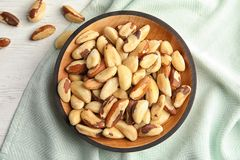 Plate with Brazil nuts and fabric on wooden table. Top view royalty free stock photography