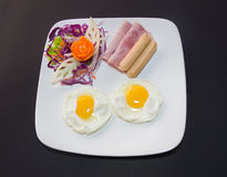 Plate of breakfast with fried eggs, bacon and toasts isolated ba Royalty Free Stock Image