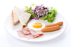 Plate of breakfast with fried eggs, toast, ham, sausage and vegetables Royalty Free Stock Images