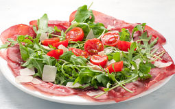 Plate of bresaola with rocket parmesan and cherry tomatoes italy Stock Photo