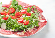 Plate of bresaola with rocket parmesan and cherry tomatoes italy Royalty Free Stock Photography