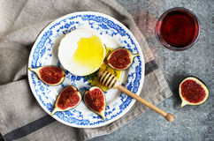 Plate with brie cheese, honey and figs and glass of red wine Royalty Free Stock Images