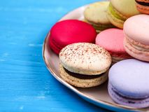 A plate of brightly colored French macarons. Traditional brightly colored French macaroons on a hand-made plate, set on a blue wooden board, close-up view Royalty Free Stock Images