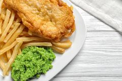 Plate with British traditional fish and potato chips on wooden background royalty free stock photo