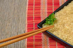 Plate with brown uncooked rice and leaf of parsley Stock Photography