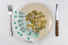 On plate is a bunch of Russian ten-thousandths of bills and coins lay near cutlery, top view. On the plate is a bunch of Russian ten-thousandths of bills and stock images