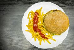 A plate with a burger, french fries and ketchup. View from above stock photos