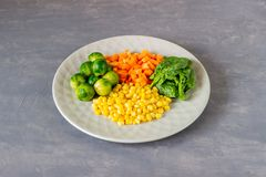 Plate with cabbage, carrots, corn and spinach. Healthy eating. Food fresh vegetarian vegan background organic raw vegetable salad colorful mix overhead stock photography