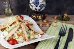 A plate with Caesar salad with chicken next to a green towel and cutlery.  royalty free stock images