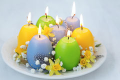 Plate with candles in the shape of easter eggs Royalty Free Stock Photo