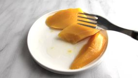 Plate of canned mangos being eaten stock footage