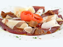 Plate of Carpaccio. Dish with thinly sliced raw beef and parmesan cheese isolated over white Royalty Free Stock Photos