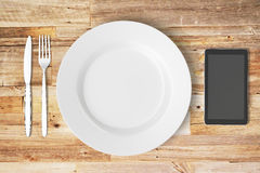 Plate and cell phone on a wooden table. Mock up royalty free illustration