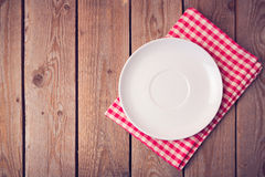 Plate on checked tablecloth over wooden background. View from above Royalty Free Stock Photo