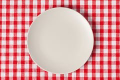 Plate on checkered table cloth Royalty Free Stock Photo