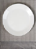 Plate on checkered table cloth. White plate on checkered table cloth - kitchen background Royalty Free Stock Photo