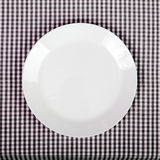 Plate on checkered table cloth. White plate on checkered table cloth - kitchen background Stock Image
