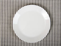 Plate on checkered table cloth. White plate on checkered table cloth - kitchen background Stock Images