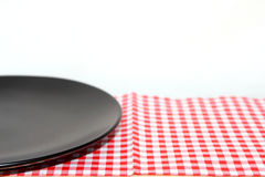The plate on checkered tablecloth Stock Images