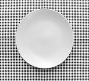 The plate on checkered tablecloth Stock Photos