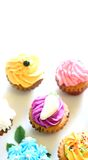 A plate of cheerful mini cupcakes. With assorted decoration and colors, with copyspace Royalty Free Stock Image
