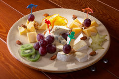 Plate with cheese. Plate with camembert, roquefort, cheese, fruits and nuts Stock Images