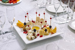 Plate of cheese and fruit. White plate served on the table Royalty Free Stock Photography