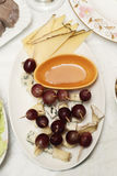Plate of cheese, grapes and honey on the holiday table Royalty Free Stock Photos