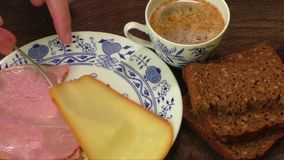 Plate with cheese,ham,cup of coffee on wooden table stock footage