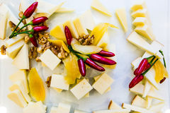 Cheese and peppers. A plate of cheese, peppers and walnuts on a buffet table Stock Photo