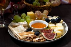 plate of cheeses, snacks and wine on a dark background Royalty Free Stock Images