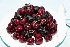Plate of cherries and blackberries royalty free stock photo