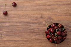 A plate of cherries. A bowl of cherries on the wooden table, healthy snack stock images