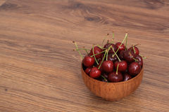 A plate of cherries. A bowl of cherries on the wooden table, healthy snack stock photography