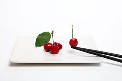 Plate with cherries and chopsticks Stock Photos