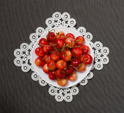 Plate with cherries on lacy napkin on a gray background, view from above Stock Image
