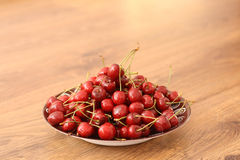 A plate of cherries. On the wooden table, healthy snack stock photography