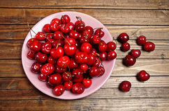 Plate with cherries on wooden table Stock Photos