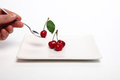 Plate with cherry spoon Stock Image